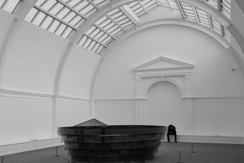 A pessoa sentou-se apenas na corte central em Leeds Art Gallery foto de stock royalty free