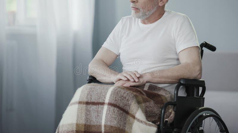 Pessoa superior doente que senta-se na cadeira de rodas, pensando sobre a vida, apoio das necessidades do homem imagem de stock royalty free