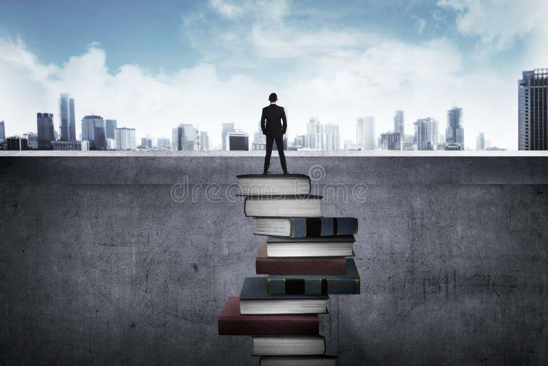 Pessoa traseira do negócio da vista que olha a cidade, estando na parte superior do livro foto de stock royalty free