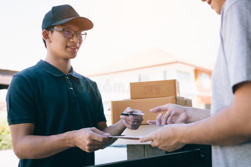 Pessoal asiático novo da entrega que mantém a pena e os documentos que submetem a doação ao cliente que recebe o pacote na casa d imagem de stock