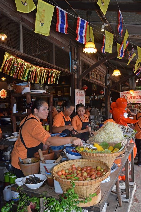 Pessoal da cozinha que ajuda a preparar o alimento tradicional no mercado de flutuação em Banguecoque, Tailândia imagem de stock royalty free