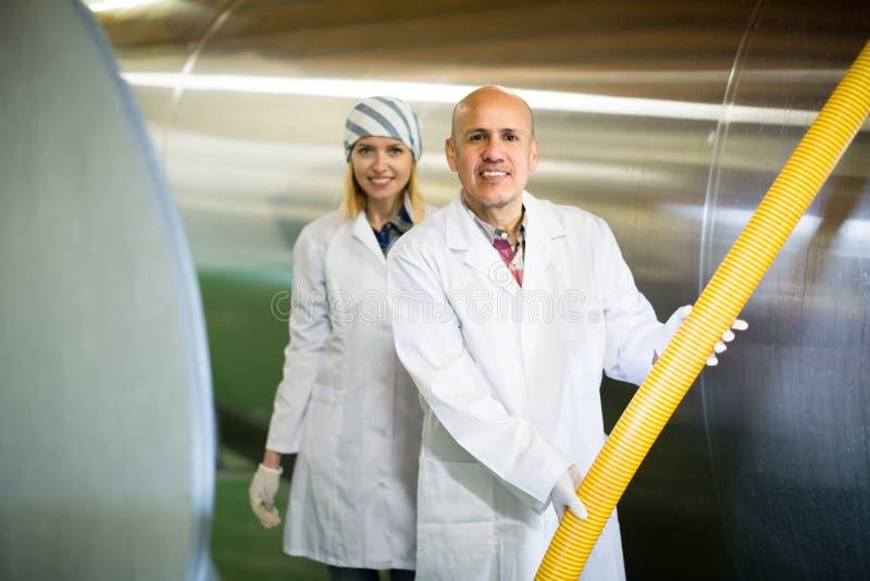 Pessoal da exploração agrícola com os reservatórios do leite na planta imagem de stock royalty free