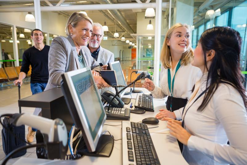 Pessoal de Looking At Female da mulher de negócios no registro do aeroporto imagens de stock royalty free