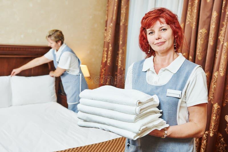 Pessoal do hotel na limpeza e nas tarefas domésticas da sala foto de stock