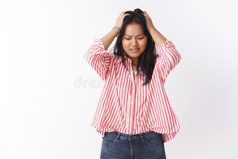 Pessoal fêmea bonito preocupado ansioso e incomodado em blusa listrada que sente cabeça nervosa e perplexo da garra com mãos fotos de stock