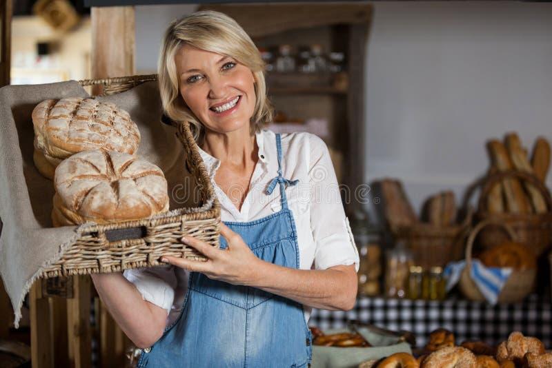 Pessoal fêmea que guarda a cesta de alimentos doces na seção da padaria fotografia de stock royalty free
