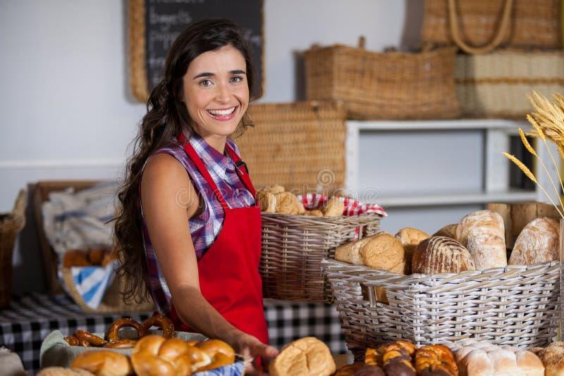 Pessoal fêmea que guarda a cesta de alimentos doces na seção da padaria imagens de stock royalty free