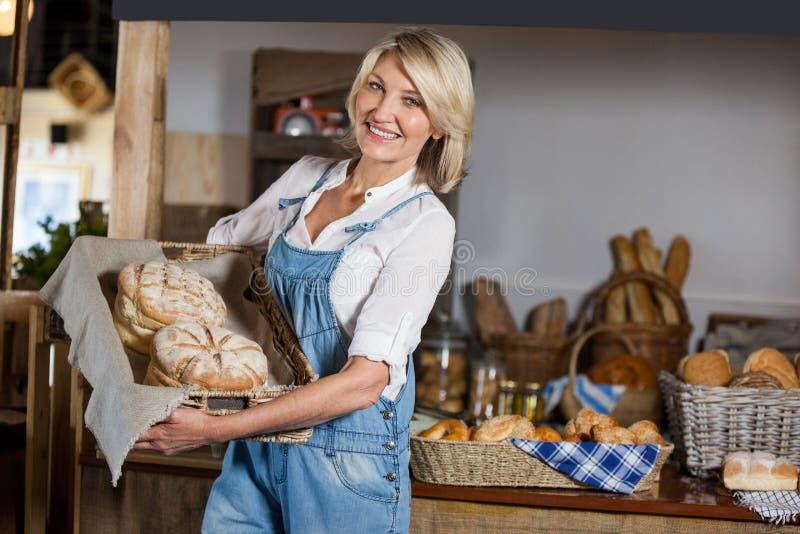 Pessoal fêmea que guarda a cesta de alimentos doces na seção da padaria imagem de stock royalty free