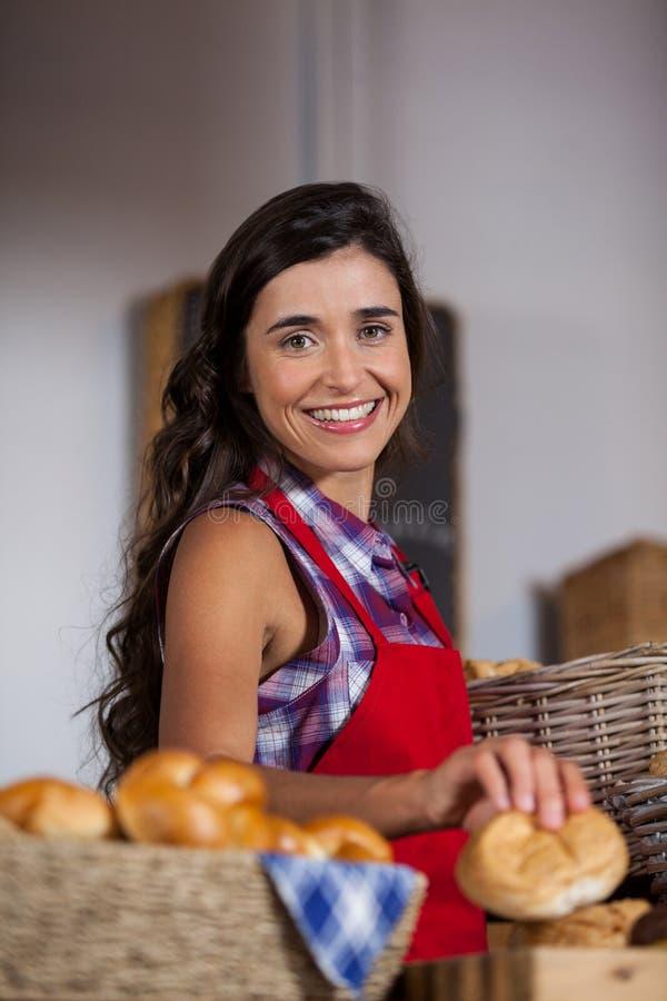 Pessoal fêmea que guarda a cesta de alimentos doces na seção da padaria imagem de stock