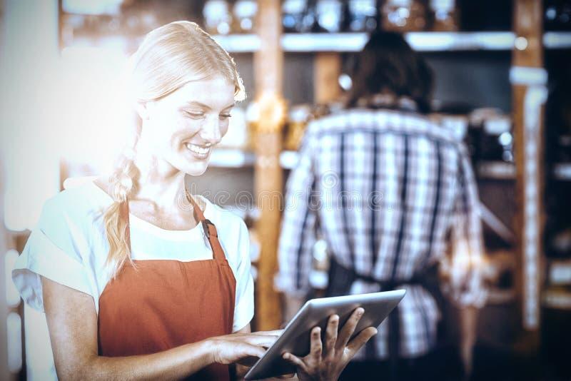 Pessoal fêmea que usa a tabuleta digital no supermercado fotografia de stock royalty free
