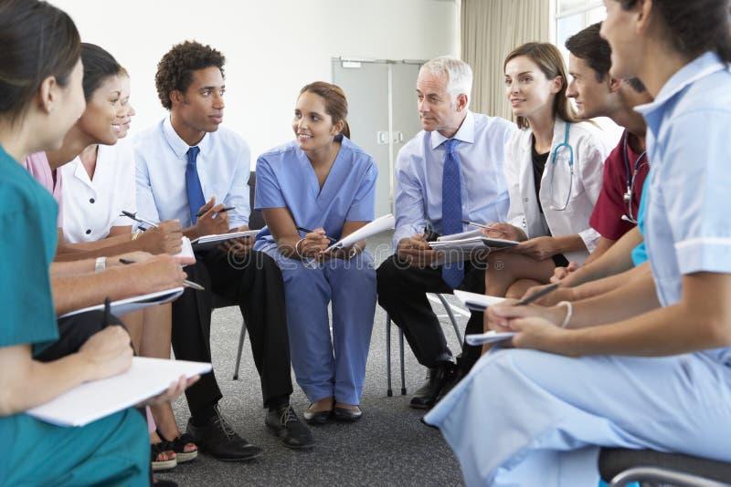 Pessoal médico assentado no círculo na reunião do caso fotografia de stock royalty free