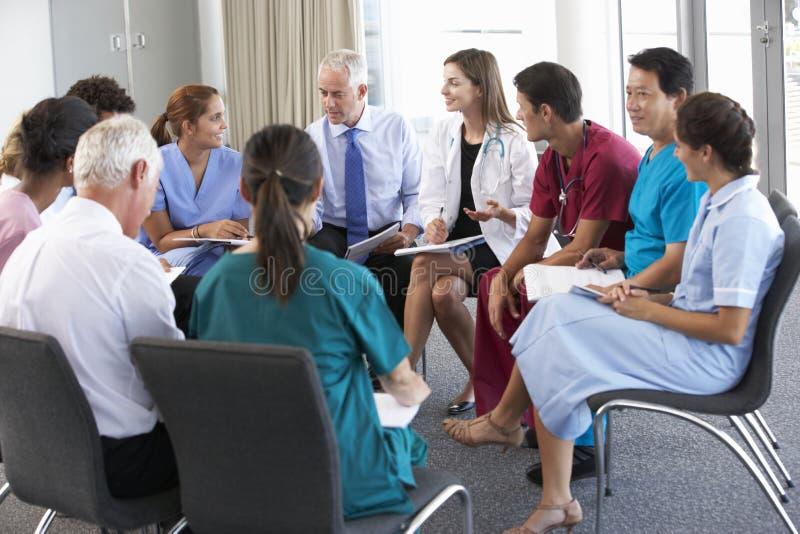 Pessoal médico assentado no círculo na reunião do caso imagem de stock