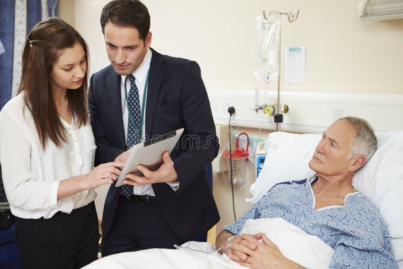 Pessoal médico nos círculos que estão pela cama do paciente masculino imagens de stock royalty free