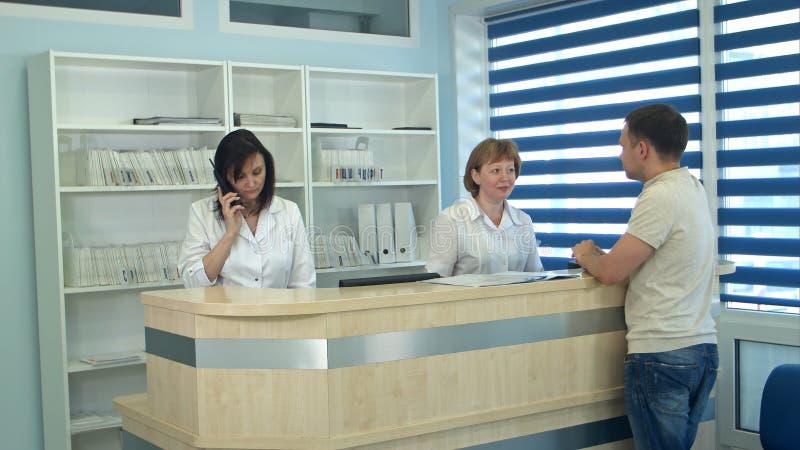 Pessoal médico que trabalha na mesa de recepção médica ocupada fotografia de stock royalty free