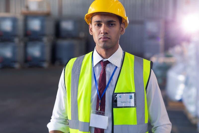 Pessoal masculino no capacete de segurança e posição reflexiva do revestimento no armazém fotografia de stock royalty free