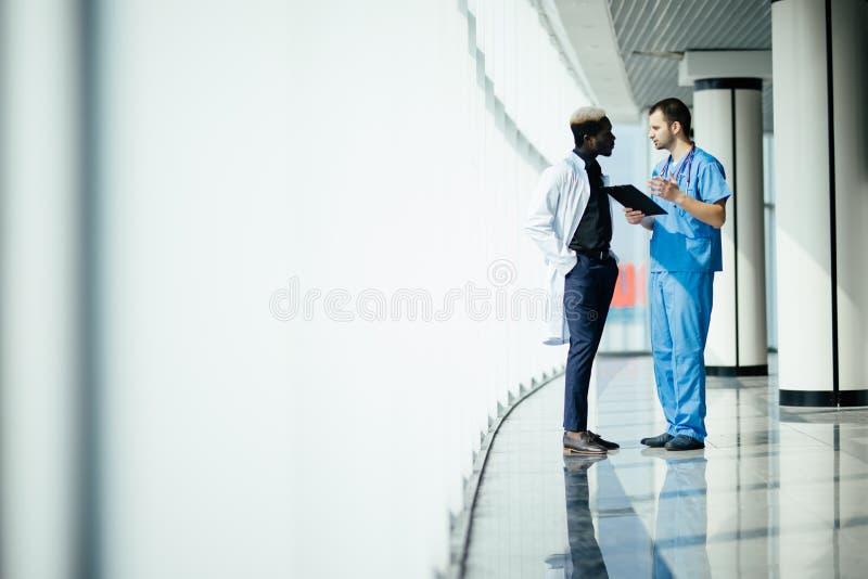 Pessoal multi-étnico médico que tem a discussão em um corredor do hospital Dois doutores que trabalham em uma clínica médica Dois foto de stock
