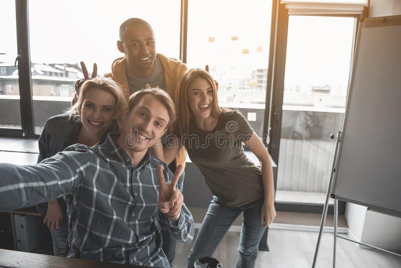 Pessoal satisfeito que toma o selfie no escritório imagens de stock