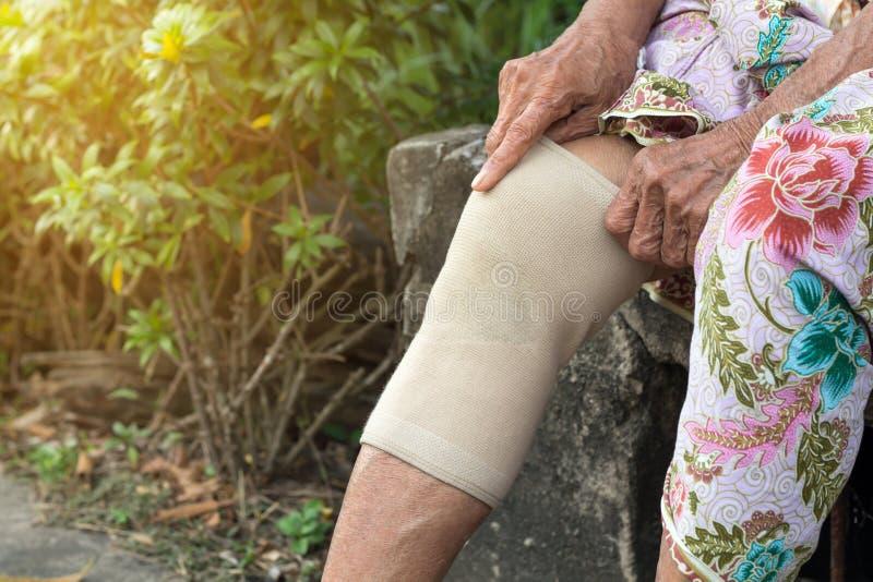 Pessoas adultas asiáticas ou mulher mais idosa que vestem a correia do joelho do apoio ou do atleta do joelho para diminuir a dor imagens de stock