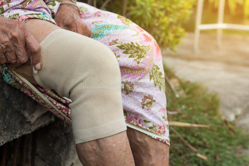 Pessoas adultas asiáticas ou mulher mais idosa que vestem a correia do joelho do apoio ou do atleta do joelho para diminuir a dor imagem de stock