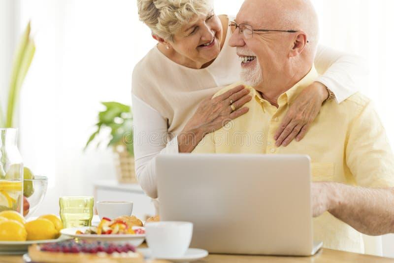 Pessoas adultas felizes que usam o portátil ao comer o café da manhã imagens de stock royalty free