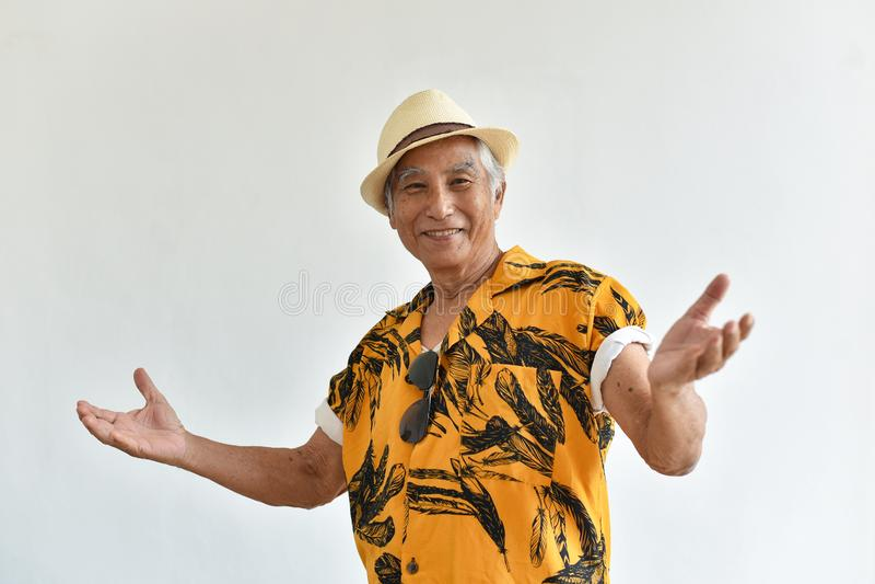 Pessoas adultas superiores asiáticas alegres do ancião, as seguras e do sorriso com gesto bem-vindo na camisa colorida de Havaí imagem de stock royalty free