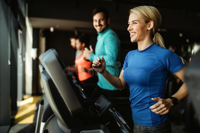 Pessoas correndo em esteira no ginásio fazendo exercícios de cardio fotos de stock