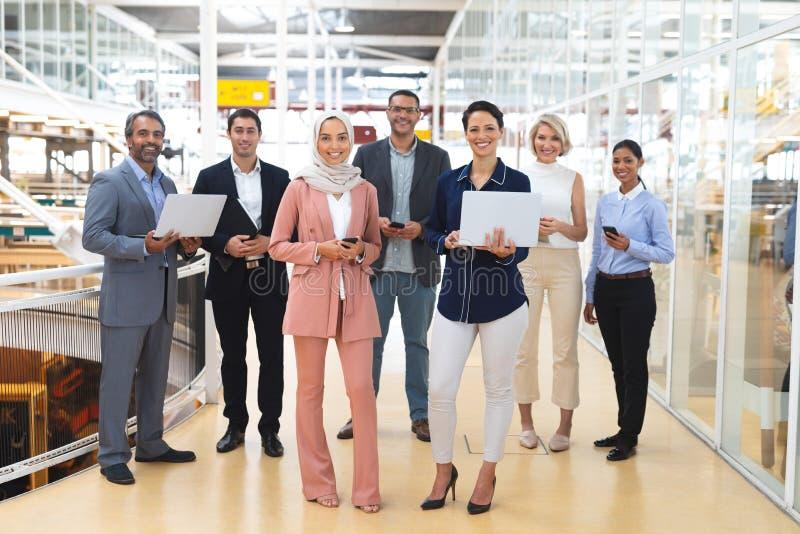 Pessoas de negócios com dispositivos multimídia olhando para uma câmera em um escritório moderno imagem de stock royalty free