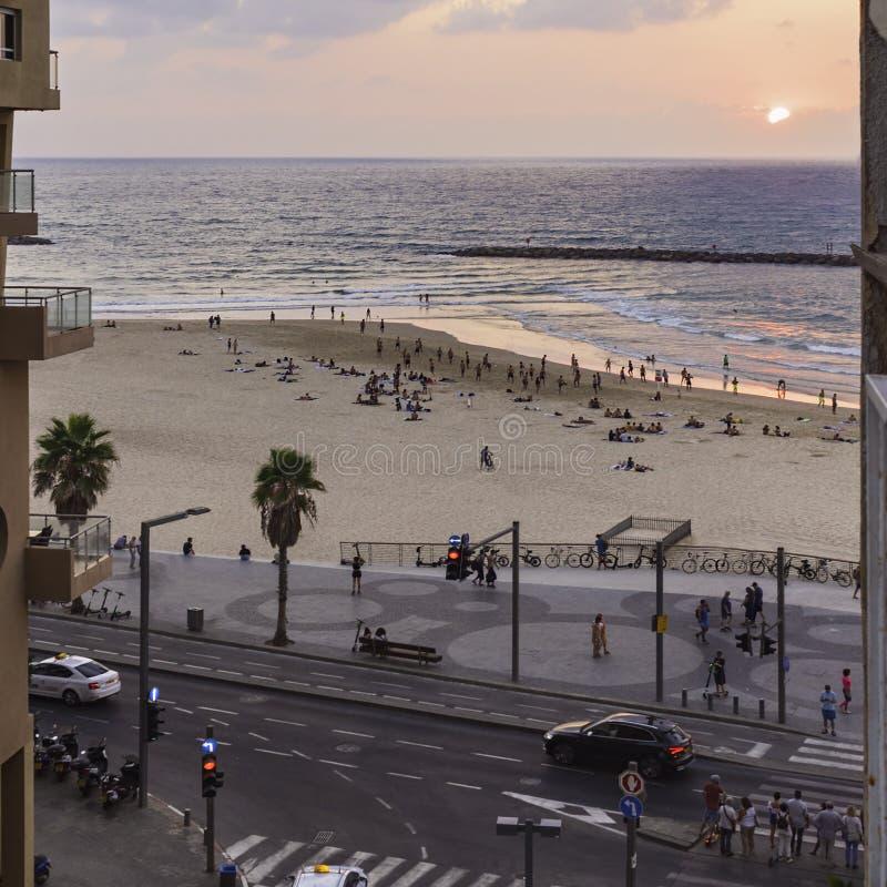 Pessoas desfrutando de um pôr do sol em uma praia de Tel Aviv de um Hostel Balcony imagens de stock royalty free