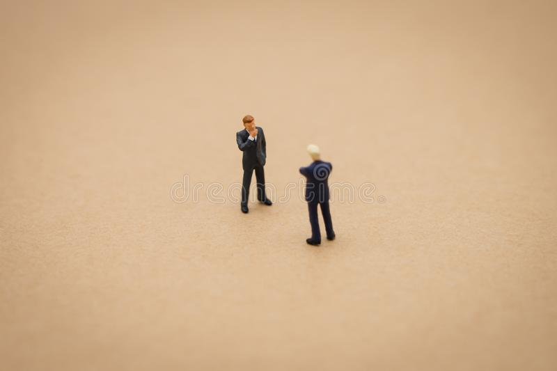 2 pessoas diminutas da posição dos homens de negócios com a parte traseira que negocia no negócio r imagem de stock