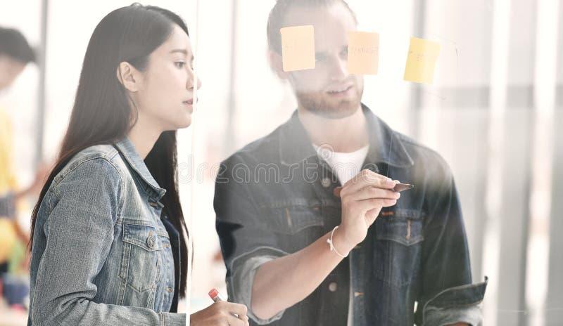 Pessoas do negócio que discutem o trabalho em uma placa de vidro fotos de stock