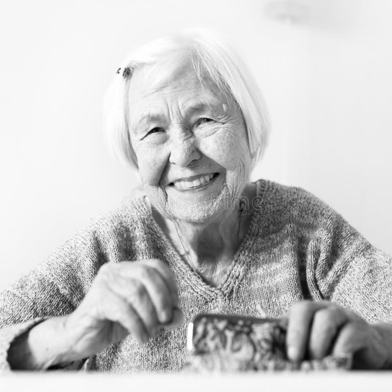Pessoas idosas alegres 96 anos de mulher adulta que senta-se na tabela em casa feliz com suas economias da pensão em sua carteira foto de stock