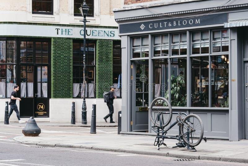Pessoas passando pelo salão de cabelos Cult & Bloom em Shoreditt, Londres, Reino Unido fotos de stock royalty free
