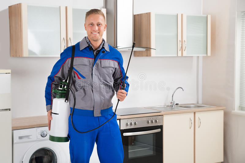 Pest Control Worker With Insecticide Sprayer. Young Happy Pest Control Worker With Insecticide Sprayer In Kitchen Room royalty free stock image