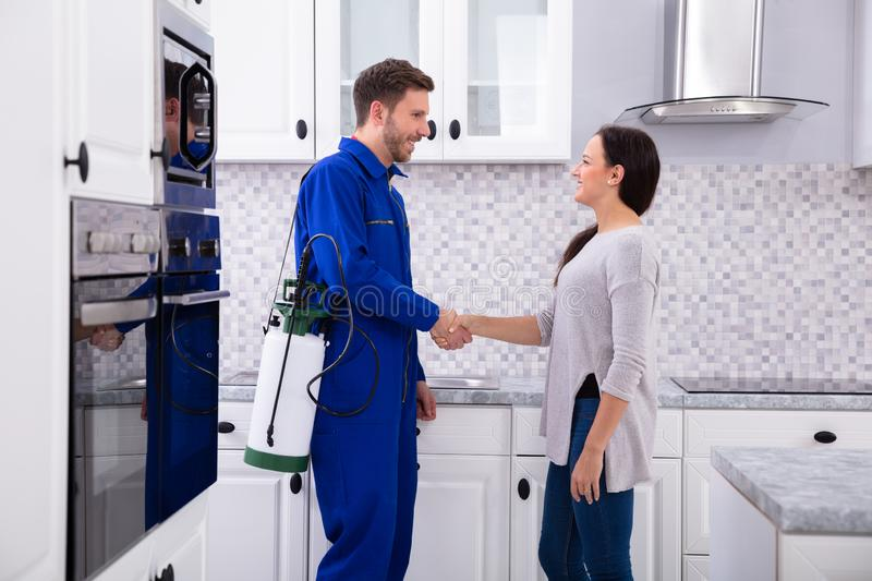 Pest Control Worker Shaking Hands With Woman. Male Pest Control Worker Shaking Hands With Happy Woman In Kitchen royalty free stock image