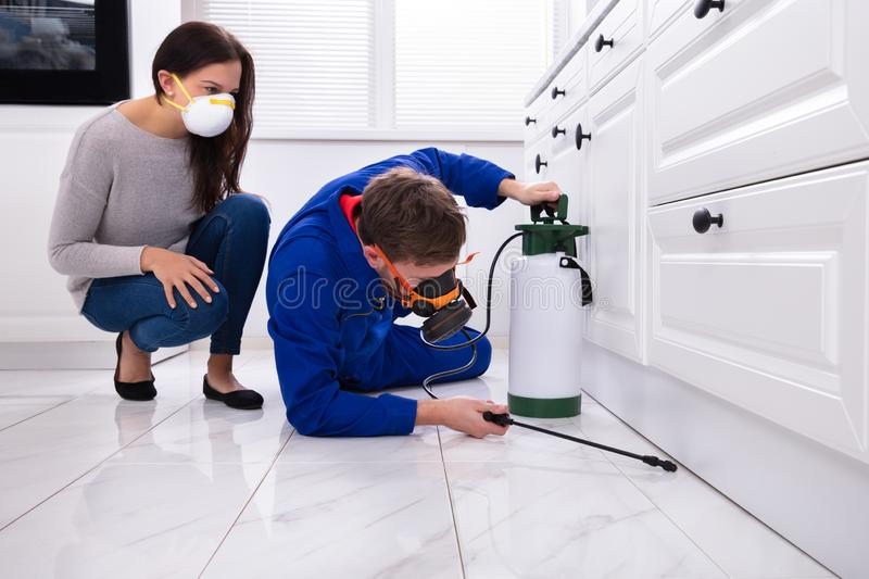 Pest Control Worker Spraying Pesticide On Wooden Cabinet. Woman Looking At Male Pest Control Worker Spraying Pesticide On Wooden Cabinet royalty free stock photos