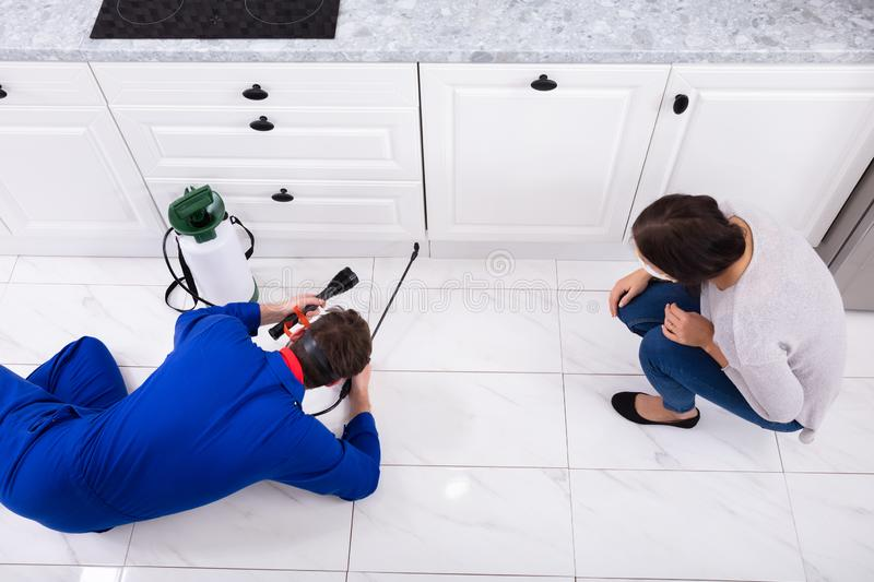 Pest Control Worker Spraying Pesticide On Wooden Cabinet. Woman Looking At Male Pest Control Worker Spraying Pesticide On Wooden Cabinet royalty free stock image