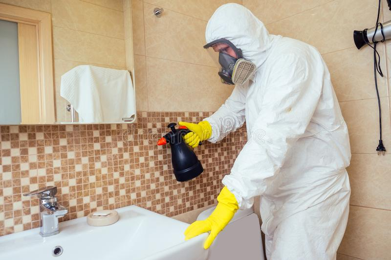 Pest control worker spraying pesticides with sprayer in bathroom:processing the toilet and shower.  royalty free stock images