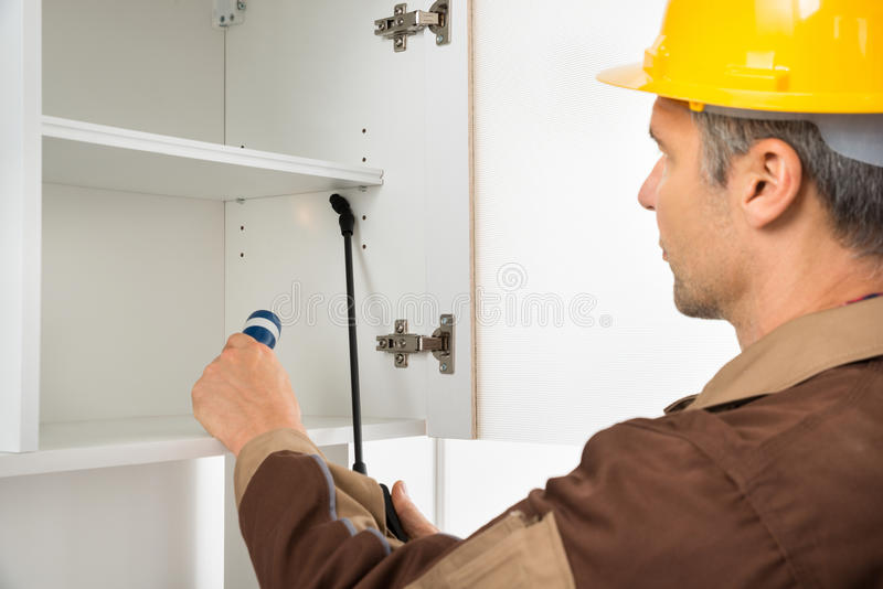 Pest control worker wearing hardhat spraying pesticides stock photography