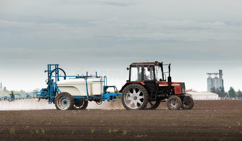 Pesticidas de rociadura del tractor en el campo de trigo fotos de archivo