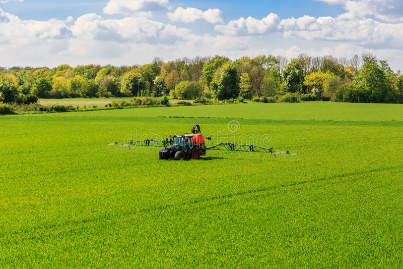Pesticides de pulvérisation de glyphosate de tracteur sur un champ images stock