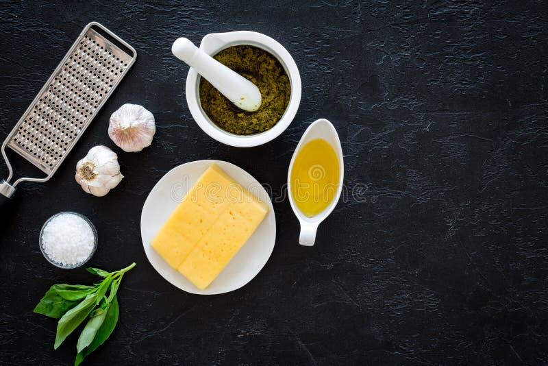 pesto调味汁的成份 乳酪、大蒜、绿色蓬蒿、橄榄油、sait在磨丝器附近和灰浆在黑背景冠上 图库摄影
