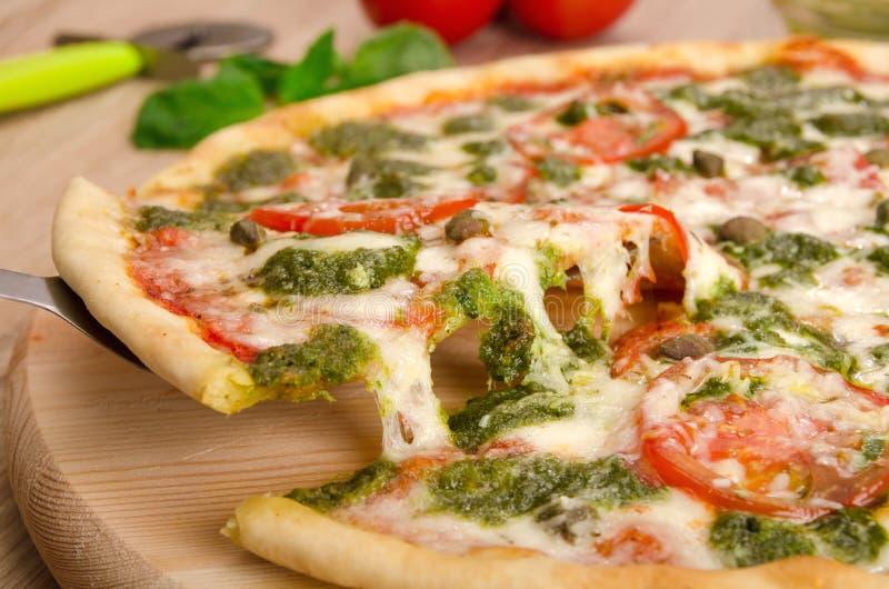 Pesto пиццы с томатами и каперсами, куском пиццы с протягивать сыра стоковая фотография rf