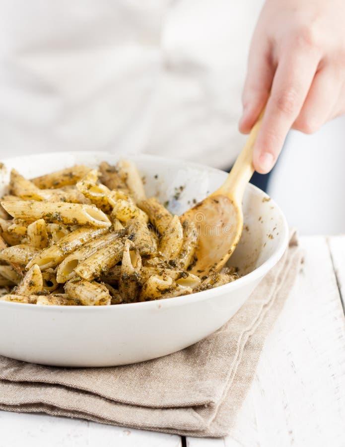 Pesto de mezcla del cocinero con las pastas del rigate del penne imagen de archivo