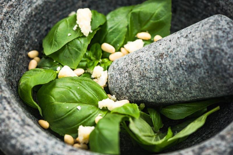 Pesto del basilico con i pinoli in mortaio del granito fotografia stock libera da diritti