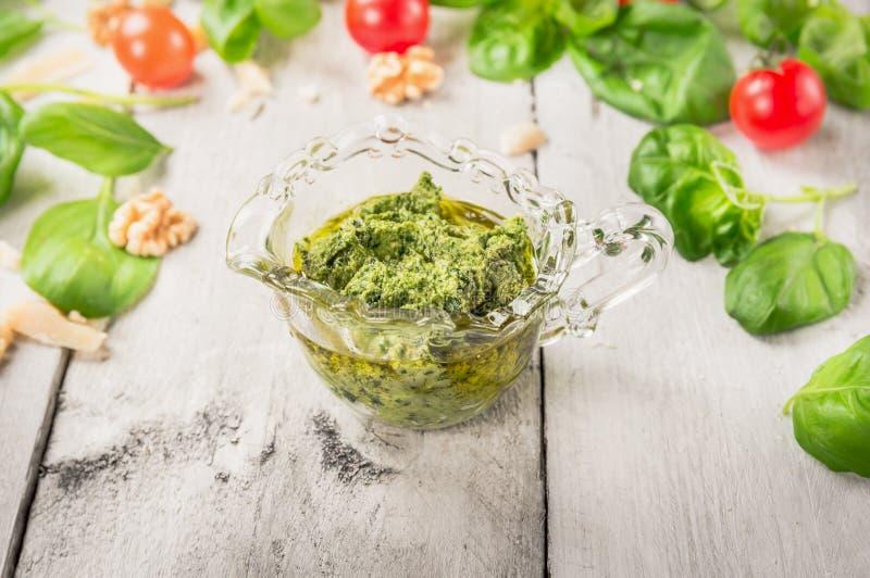 Pesto del basilico in tazza di vetro sopra i pomodori, la noce ed il parmigiano su di legno bianco fotografia stock libera da diritti