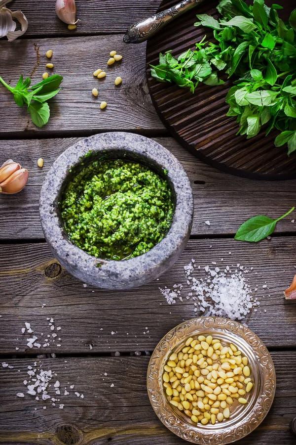 Pesto en mortier, sel, nuta de pin et ail de marbre sur la table en bois photos stock