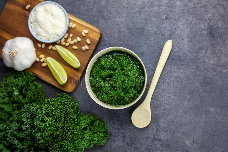 Pesto from kale. Kale, cheese, lemon, pine nuts and garlic on the background - top view. Pesto from kale. Kale, cheese, lemon, pine nuts and garlic on the wooden stock images