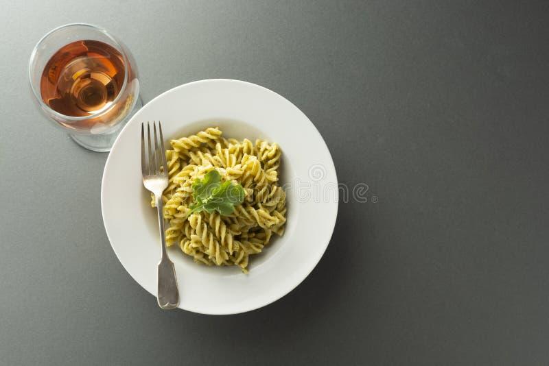 Pesto Pasta and rose wine glass in white plate over gray background. Italian food. Pesto Pasta in white plate over gray background, fusili ,spaghetti. Italian stock image
