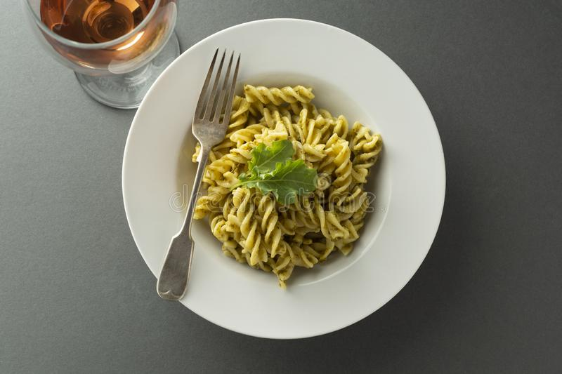 Pesto Pasta and rose wine glass in white plate over gray background. Italian food royalty free stock photography