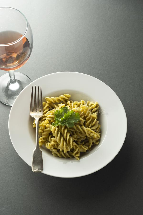 Pesto Pasta and rose wine glass in white plate over gray background. Italian food stock photography
